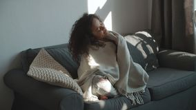 Happy beautiful woman sitting on sofa wrapped in blanket relaxing at home. stock footage