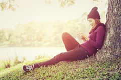Happy beautiful woman sitting under the tree playing mobile phon. E in the park and background Royalty Free Stock Photo