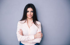 Happy beautiful woman standing with arms folded Royalty Free Stock Image