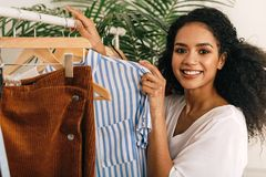 Happy beautiful woman standing at clothes rack stock images
