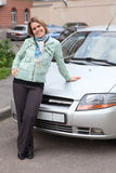Happy beautiful woman standing in front of new car Royalty Free Stock Images