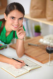 Happy beautiful woman standing in her kitchen Stock Image