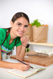 Happy beautiful woman standing in her kitchen Stock Photo