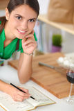 Happy beautiful woman standing in her kitchen Stock Photos