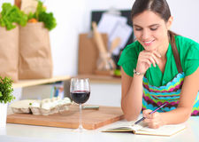 Happy beautiful woman standing in her kitchen writing on a notebook at home Stock Image