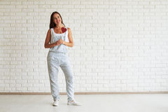 Happy beautiful woman standing and holding red paper heart. Happy beautiful brunette dressed in strip overalls, standing and holding red paper heart, white brick Stock Image