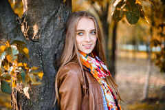 Happy beautiful woman standing near the tree in the autumn Royalty Free Stock Image
