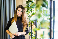 Happy beautiful woman standing at office wall with notebook. business people. Royalty Free Stock Image