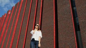 Happy beautiful woman stands on city street near a modern brick building, exhibition center stock footage