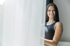 Happy beautiful woman staring out the window. Happy beautiful young woman staring out the window Stock Photography