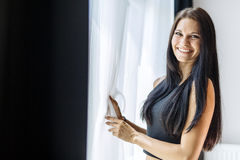 Happy beautiful woman staring out the window. Happy beautiful young woman staring out the window Stock Images