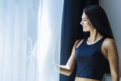 Happy beautiful woman staring out the window. Happy beautiful young woman staring out the window Royalty Free Stock Images