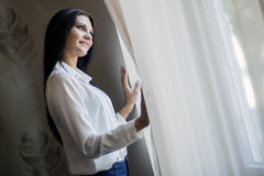 Happy beautiful woman staring out the window. Happy beautiful young woman staring out the window and holding curtains Royalty Free Stock Images