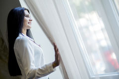 Happy beautiful woman staring out the window. Happy beautiful young woman staring out the window and holding curtains Stock Photography
