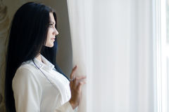 Happy beautiful woman staring out the window. Happy beautiful young woman staring out the window and holding curtains Stock Images