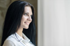 Happy beautiful woman staring out the window. Happy beautiful young woman staring out the window and holding curtains Stock Image