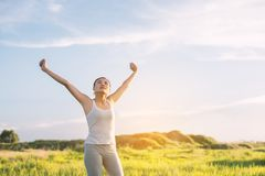 Happy beautiful woman with stretched arms in meadows with fresh. Air stock photography