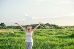 Happy beautiful woman with stretched arms in meadows with fresh. Air background stock photos