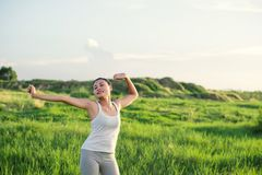 Happy beautiful woman with stretched arms in meadows with fresh. Air background royalty free stock photography