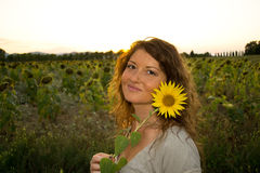 Happy beautiful woman with sunflower. Happy beautiful woman with bright sunflower in sunflower field Royalty Free Stock Image