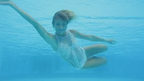 Happy beautiful woman swimming underwater in swimming pool. She smiles. And doing acrobatic tricks and spins stock video footage