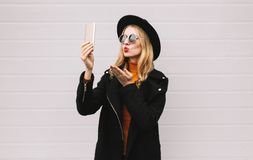 Happy beautiful woman taking selfie picture by smartphone. Fashion, technology and people concept - happy beautiful woman taking selfie picture by smartphone stock photo