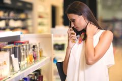 Happy beautiful woman testing perfumes. In cosmetics store stock photo