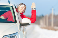 Happy beautiful woman travels by car in winter. Royalty Free Stock Photos