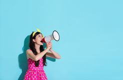 Happy beautiful woman using megaphone speaking. Information and wearing pink cute dress in blue wall background Stock Images