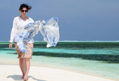 Happy beautiful woman walking at the beach with white sand Royalty Free Stock Photos