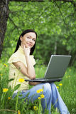 Happy beautiful woman working outdoors. Young woman sitting on the grass with laptop on her knees and thinking about the future or past Royalty Free Stock Image