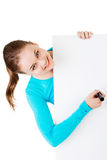 Happy beautiful woman writing with a pen on blank board. Royalty Free Stock Photography