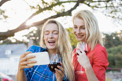 Happy beautiful women looking at mobile phone stock image