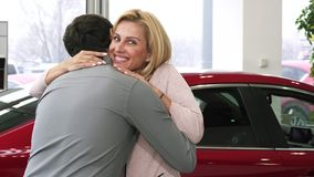 Gorgeous happy mature woman receiving car keys from her loving husband royalty free stock photography