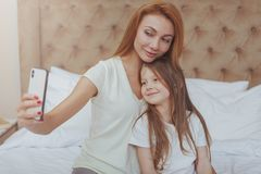 Beautiful woman and her little daughter using smart phone royalty free stock images