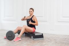 Happy beautiful young athletic causcasian woman pink shorts and black top siting, drink water and have a rest after hard working. On the gym. Indoor, studio stock photos