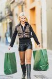 Happy Beautiful young blonde girl holding two green paper packages. Walking on Shopping europian street royalty free stock photography