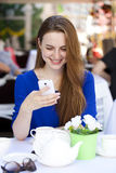 Happy Beautiful young blonde woman reads a message on your smart Royalty Free Stock Images