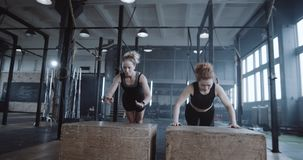 Happy beautiful young blonde woman working out together with personal female coach in big gym doing push-ups slow motion. Motivation and healthy lifestyle, two stock footage