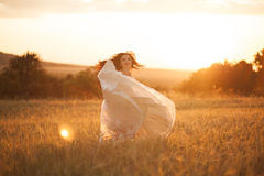 Happy beautiful young bride outside on a summer meadow at the sunset Royalty Free Stock Image