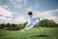 Happy and beautiful young brunette girl jumping high Royalty Free Stock Photo