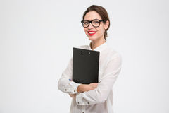 Happy beautiful young business woman standing and holding clipboard Stock Photo
