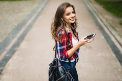 Happy beautiful young caucasian high school girl with green smart phone outdoors on sunny Royalty Free Stock Photo