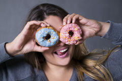 Happy beautiful young caucasian plus size model posing with donuts on a gray studio background Stock Image