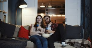 Happy beautiful young Caucasian romantic couple talking, watching fun movie at home with drinks and popcorn slow motion. stock footage