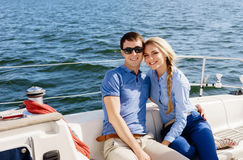 Happy and beautiful young couple having a rest on a yacht. Trave Stock Photo