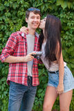 Happy beautiful young couple near green wall with camera. looking at camera. Happy beautiful young couple near green wall with camera. looking at camera with Stock Image