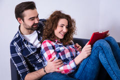 Happy beautiful young couple reading book on sofa Royalty Free Stock Photo