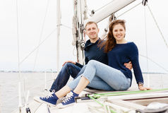 Happy and beautiful young couple sitting on deck and having a go Stock Images