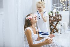 Happy beautiful young family mother and daughter smile and play. House with the flowers Stock Photography
